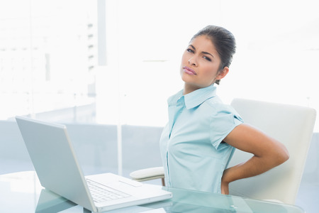 back ache: Young businesswoman suffering from back ache in front of laptop in the office Stock Photo