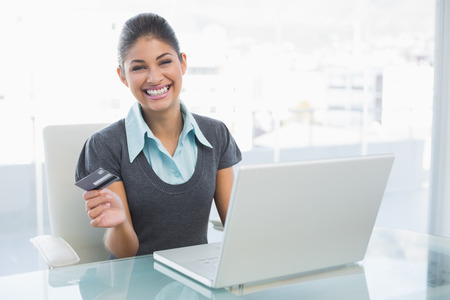 Portrait of a smiling businesswoman doing online shopping through laptop and credit card photo