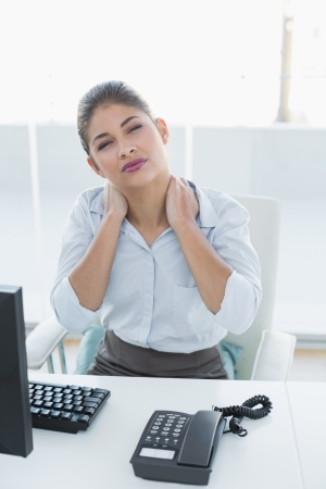 Young businesswoman with neck pain in front of computer in office photo