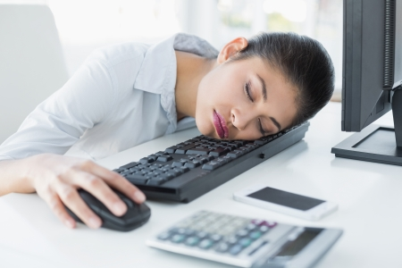Young businesswoman resting head on keyboard in the office photo