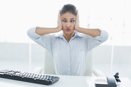 tied down: Young businesswoman suffering from headache in front of computer at a bright office