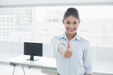 Portrait of a smiling young businesswoman gesturing thumbs up at bright office photo