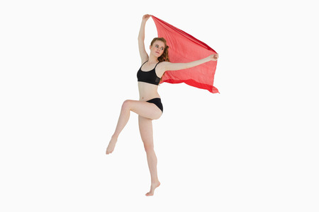 Full length of a sporty young woman holding red fabric over white background photo