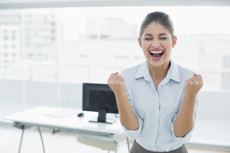 clenching fists: Elegant and happy businesswoman clenching fists in a bright office