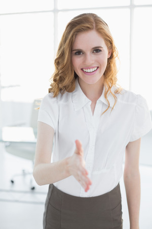 Portrait of an elegant businesswoman offering a handshake in the office photo
