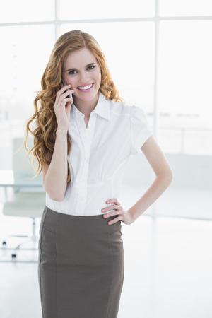 Portrait of an elegant businesswoman using mobile phone in a bright office