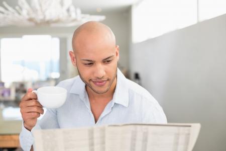Concentrated young man having coffee while reading newspaper at home photo