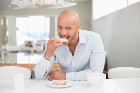 Portrait of a handsome young man having breakfast at home photo