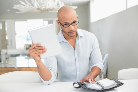 Portrait of a casual serious young man with digital tablet and diary at home Stock Photo