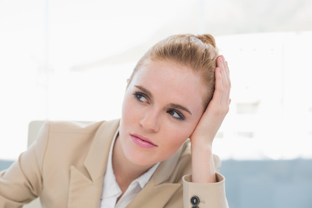 Thoughtful businesswoman looking away in a bright office photo
