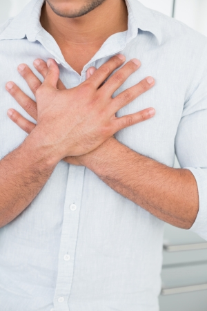 Close up mid section of a young man with chest pain photo