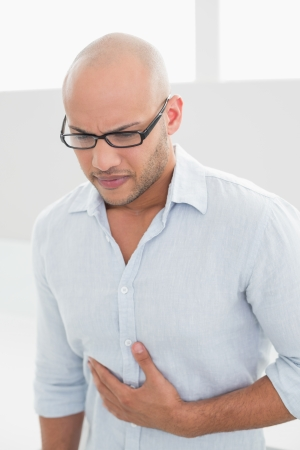 Casual young man suffering from chest pain standing at home
