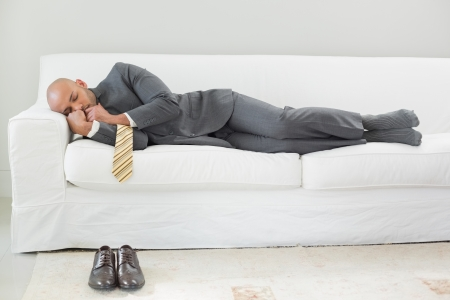 Full length of an elegant businessman sleeping on sofa at home photo