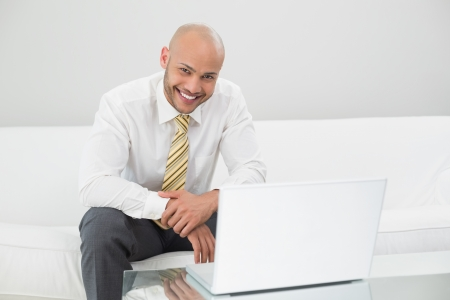 Portrait of a smiling elegant young businessman using laptop on sofa at home photo