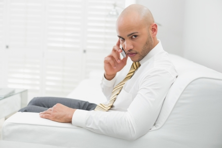 Side view portrait of a serious elegant young businessman using cellphone on sofa at home photo