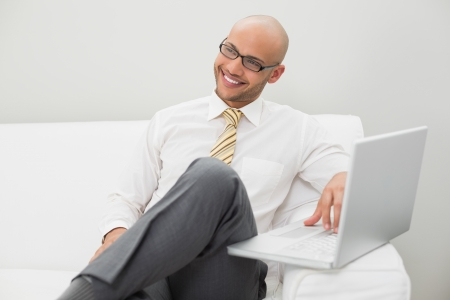 Smiling elegant young businessman using laptop on sofa at home photo