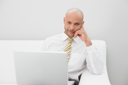 Portrait of a smiling elegant young businessman with laptop sitting on sofa at home photo