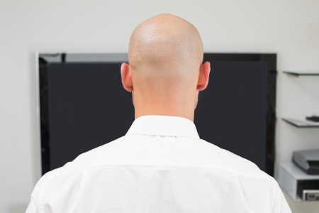 Close up rear view of a bald man using computer at office photo