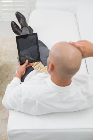 bald man: Vista de ángulo alto de un joven hombre de negocios calvo que usa la tableta digital en el sofá en casa