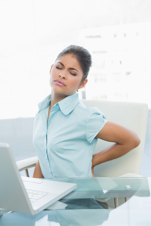 Young businesswoman suffering from back ache in front of laptop in the office Stock Photo