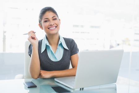 Portrait of a smiling businesswoman with laptop sitting at a bright office photo