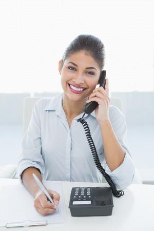 Portrait of an elegant businesswoman using telephone at desk against white background photo