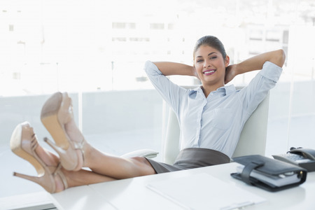 tied hair: Portrait of a relaxed young businesswoman sitting with legs on desk in a bright office