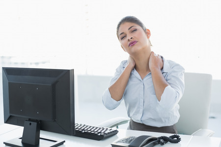 Young businesswoman with neck pain in front of computer against white background photo