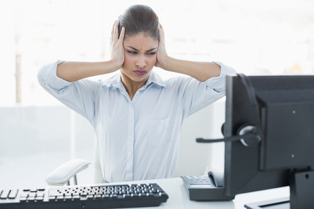 Young businesswoman suffering from headache in front of computer at a bright office photo