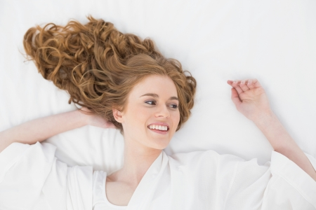 fair woman: Overhead view of a smiling young blond lying in bed at home