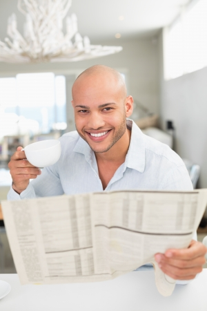 Portrait of a smiling young man with coffee cup reading newspaper at home photo