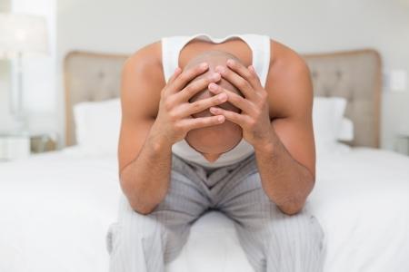 hombre pensando: Hombre calvo joven pensativo sentado con la cabeza en las manos sobre la cama en su casa Foto de archivo
