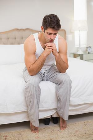 pies masculinos: Longitud total de un hombre joven pensativo sentado en la cama en su casa