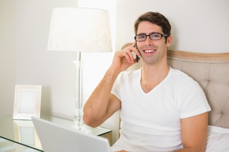 Portrait of a casual smiling young man using cellphone and laptop in bed at home photo