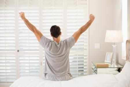 若い男がベッドで目を覚ます、腕を伸ばしての後姿 写真素材