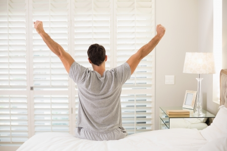 Rear view of a young man waking up in bed and stretching his arms Stock Photo