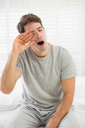Sleepy young man yawning as he rubs his eye in bed at home