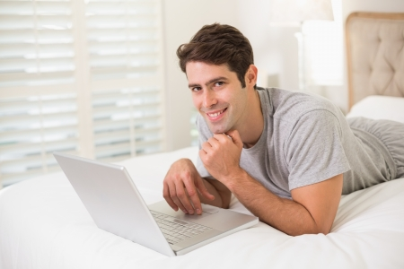 Portrait of a casual smiling young man using laptop in bed at home photo