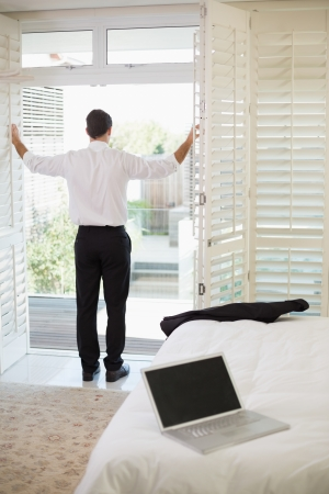 Full length of a businessman looking through window at a hotel bedroom photo