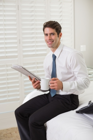 Smiling young businessman with coffee cup reading newspaper at a hotel room photo