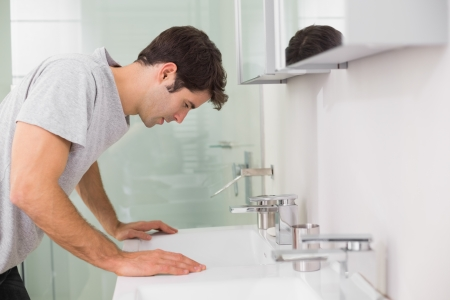 gloominess: Side view of a tensed young man at washbasin in bathroom Stock Photo