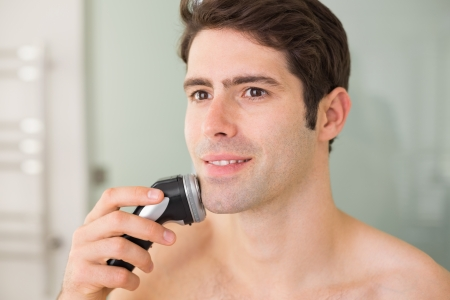 Smiling handsome young shirtless man shaving with electric razor photo