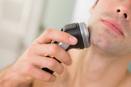 Extreme Close up of a handsome young man shaving with electric razor Stock Photo