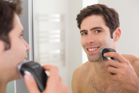 Reflection of a handsome young shirtless man shaving with electric razor photo