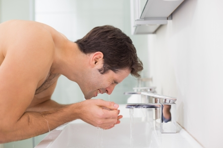 Side view of a shirtless young man washing face in the bathroom photo