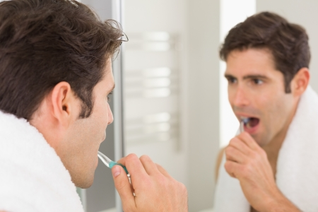 Close up of a young man with reflection brushing teeth in the bathroom photo