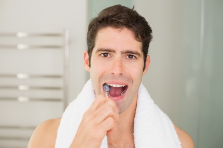 Close up portrait of a young man brushing teeth in the bathroom photo