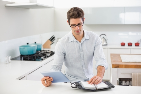 Casual serious young man with digital tablet using a diary in kitchen at home photo