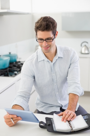Happy casual young man with digital tablet and diary in kitchen at home