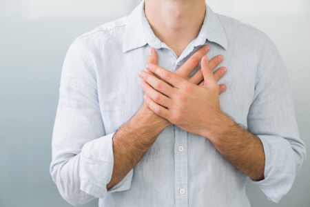 Close up mid section of a young man with chest pain